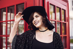 Modieus Brits portret van een charmante jonge vrouw met kort haar brunette in een modieuze hoed die onderaan de straat dichtbij l stock afbeelding