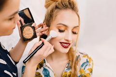 Modieus close-upportret van vrij jonge vrouw die in kappersalon aan partij voorbereidingen treffen Het maken van make-up, stilist royalty-vrije stock foto's