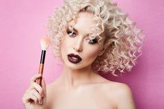 Modieus en modieus modelmeisje met blauwe ogen en krullend blond haar, met het professionele heldere make-up stellen met make-upb stock foto's