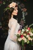 Modieus en mooi donkerbruin modelmeisje met heldere make-up en met een bloemenkroon op haar hoofd in een modieus kant stock fotografie