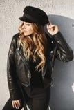 Modieus en sexy blonde modelmeisje in een zwart leerjasje, in zwarte in jeans en in modieuze hoed die en glimlachen stellen met stock afbeelding