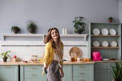 Modieus gelukkig donkerbruin meisje in slang gedrukte broeken die in de keuken dansen royalty-vrije stock fotografie