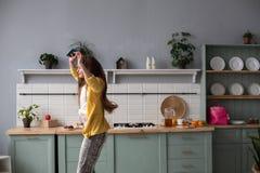 Modieus gelukkig donkerbruin meisje in slang gedrukte broeken die in de keuken dansen royalty-vrije stock afbeeldingen