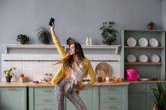 Modieus gelukkig donkerbruin meisje in slang gedrukte broeken die in de keuken dansen stock foto's
