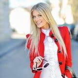 Modieus glimlachend jong meisje in rode kleding met handtas openlucht stock afbeeldingen