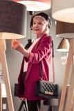 Modieus helder verouderend mevrouw die nieuwe staande lamp in verlichtingsopslag selecteren royalty-vrije stock afbeelding