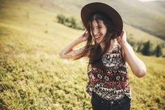 Modieus hipstermeisje in hoed die bovenop zonnige bergen en het glimlachen reizen Portret van gelukkige jonge vrouw met mooi haar royalty-vrije stock afbeeldingen