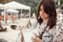 Modieus hipstermeisje ongelukkig met woknoedels met groenten van van het kartondoos en bamboe eetstokjes Het Aziatische festival  royalty-vrije stock foto