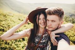Modieus hipsterpaar die selfie en bovenop onderstel glimlachen nemen royalty-vrije stock afbeeldingen