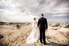Modieus huwelijkspaar die zich op overzeese kust bevinden De jonggehuwden lopen door het overzees royalty-vrije stock foto