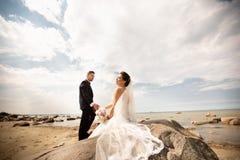 Modieus huwelijkspaar die zich op overzeese kust bevinden De jonggehuwden lopen door het overzees royalty-vrije stock fotografie