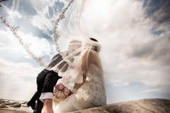 Modieus huwelijkspaar die zich op overzeese kust bevinden De jonggehuwden lopen door het overzees stock fotografie