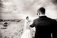 Modieus huwelijkspaar die zich op overzeese kust bevinden De jonggehuwden lopen door het overzees Rebecca 36 stock afbeeldingen
