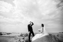 Modieus huwelijkspaar die zich op overzeese kust bevinden De jonggehuwden lopen door het overzees Rebecca 36 stock fotografie