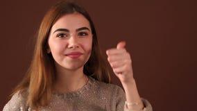 Modieus jong meisje die duim op een bruine achtergrond in de Studio tonen stock video