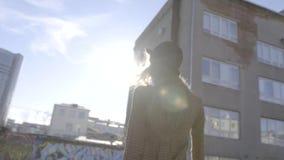 Modieus jong vrouwenmodel in hoed het stellen op camera actie Openluchtportret van jonge mooie modieuze vrouw stock footage