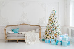 Modieus Kerstmisbinnenland met een elegante bank Comforthuis Stelt giften onderaan de boom in woonkamer voor Stock Afbeelding