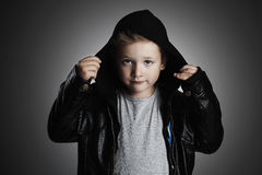 Modieus kind in leer modieuze knap weinig jongen in kap royalty-vrije stock foto's