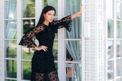 Modieus lang brunette met mooie lange benen die in een zwarte kledingsbuitenkant dichtbij een glasmuur stellen Een Aantrekkelijk  royalty-vrije stock fotografie
