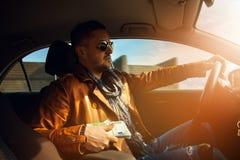 Modieus mannelijk model die een lor van geld EUR houden en auto drijven stock afbeelding