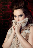 Modieus meisje in bont een bakstenen muur Royalty-vrije Stock Foto