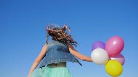 Modieus meisje die met kleurenbundel van haar en ballons in handen tegen hemel springen stock videobeelden
