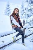 Modieus meisje in jeans, witte geborduurde blouse en multicolored wollen vest bij houten omheining stock afbeeldingen
