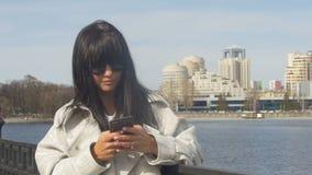 Modieus meisje met telefoon op strandboulevard stock footage