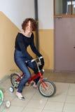 Modieus meisje op een kinderen` s fiets Stock Foto's
