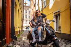 Modieus meisje in zonnebril die een leerjasje en gescheurde jeans dragen die op een zwarte klassieke autoped op oud zitten royalty-vrije stock foto