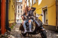Modieus meisje in zonnebril die een leerjasje en gescheurde jeans dragen die op een zwarte klassieke autoped op oud zitten stock fotografie