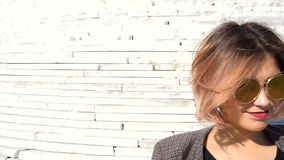 Modieus modieus jong vrouwelijk model in zonnebril in een zwarte kleding stock videobeelden