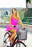 Modieus mooi jong mooi meisje in roze kleding op een bicyc royalty-vrije stock fotografie