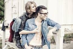 Modieus paar dat jeans en laarzen het glimlachen draagt Stock Afbeelding