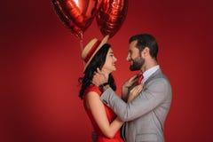 Modieus paar die met rode ballons elkaar bekijken Royalty-vrije Stock Foto