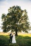 Modieus paar van gelukkige jonggehuwden die op gebied op hun huwelijksdag lopen met boeket In het midden van het gebied zijn er royalty-vrije stock fotografie