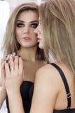 Modieus schot van een sexy mooi meisje in spiegels in zwarte kleren met de ogen van make-upsmokey royalty-vrije stock foto's