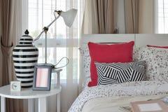 Modieus slaapkamerbinnenland met de hoofdkussens en de lamp van het bloempatroon Stock Fotografie