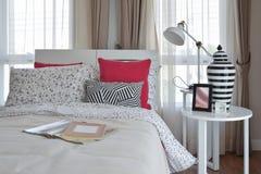 Modieus slaapkamerbinnenland met de hoofdkussens van het bloempatroon en decoratieve lamp Royalty-vrije Stock Afbeelding