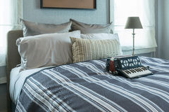Modieus slaapkamerbinnenland met gestreepte hoofdkussens en decoratieve harmonika op bed royalty-vrije stock fotografie