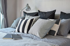 Modieus slaapkamerbinnenland met zwarte gevormde hoofdkussens op bed Stock Afbeelding