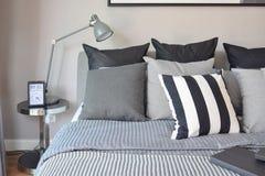 Modieus slaapkamerbinnenland met zwarte gevormde hoofdkussens op bed Royalty-vrije Stock Foto