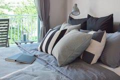Modieus slaapkamerbinnenland met zwarte gevormde hoofdkussens op bed Royalty-vrije Stock Afbeeldingen