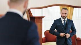 Modieus succesvol mannetje in pak die klaar voor werkdag voor uitstekende spiegel worden stock footage