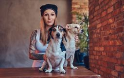 Modieus tattoed blondewijfje in t-shirt en de jeans omhelst twee leuke honden royalty-vrije stock afbeelding