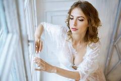 Modieus vrouwelijk portret van leuke dame in witte robe binnen Stock Foto's