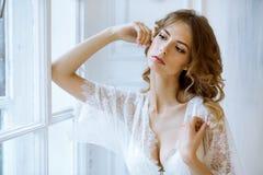 Modieus vrouwelijk portret van leuke dame in witte robe binnen Royalty-vrije Stock Foto's