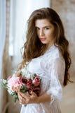 Modieus vrouwelijk portret van leuke dame in witte robe binnen Stock Foto