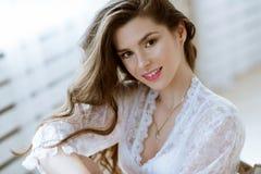 Modieus vrouwelijk portret van leuke dame in witte robe binnen Stock Afbeeldingen