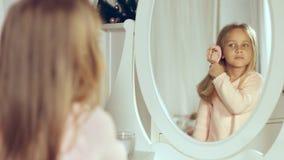 Modieus weinig dame die haar haar kammen en in de spiegel kijken Stock Afbeeldingen